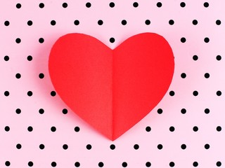 Red paper Valentines Day heart on pink polka dot background
