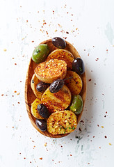 Grilled potatoes with olives in a wooden dish