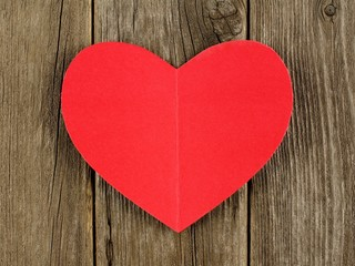 Red paper Valentines Day heart on vintage wood background