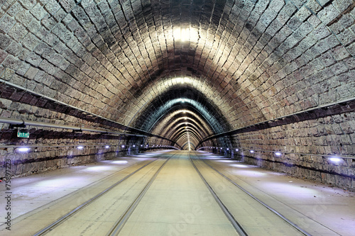 Leinwanddruck Bild Underground railroad with  moving train, transporation.