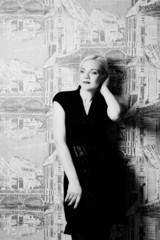 blond woman posing on wall background black and white