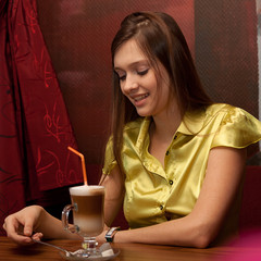 beautiful young girl with cup of latte coffee in restaurant