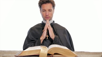 young catholic priest saying a prayer