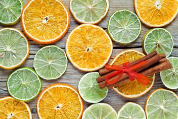 Dried orange, lemon slices and cinnamon sticks on wooden table.