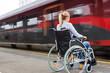 canvas print picture - Frau sitzt in einem Rollstuhl auf einem Bahnhof
