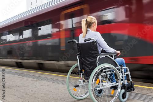 canvas print picture Frau sitzt in einem Rollstuhl auf einem Bahnhof