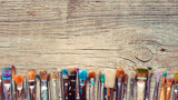Row of artist paintbrushes closeup on old wooden rustic backgrou