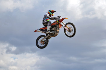 Rider by motorcycle MX flies over the hill against the blue sky