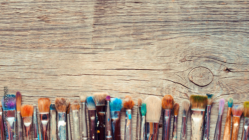 Leinwanddruck Bild Row of artist paintbrushes closeup on old wooden rustic backgrou