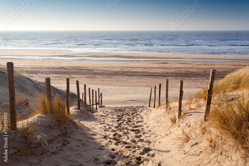 In de dag Kust sand path to North sea at sunset