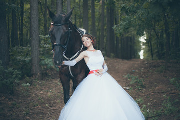Young woman in white dress standing with horse
