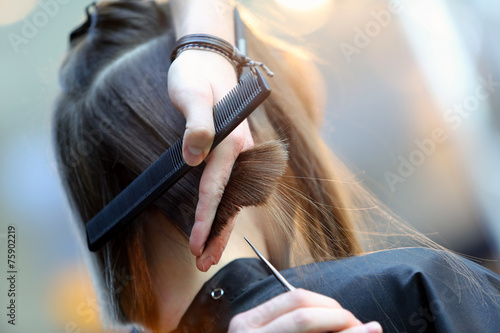 Hairdresser trimming brown hair with scissors - 75902219