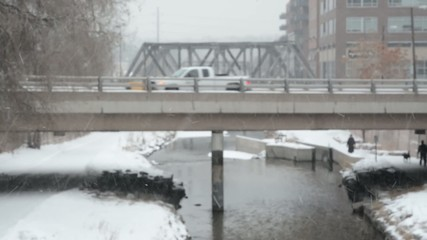Cars crossing bridge on snowy day, fades into focus