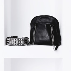 Fashion bag and belt on the shelf in white interior. Stylish acc