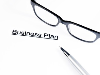 business plan words near glasses and pen, business concept