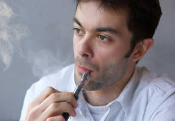 Young man smoking modern electric cigarette