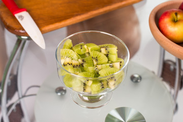 Portrait of pregnant mother cuts kiwi fruit