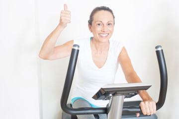 Frau auf Fitnessfahrrad mit Daumen hoch