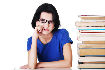Tired woman sitting at a desk with stack of books