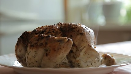 There is a fume of cooked chicken lying on a plate on the table