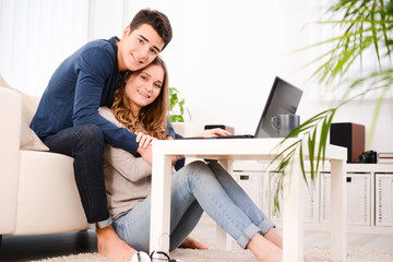 young couple at home playing on internet with a computer