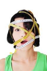 Caucasian woman with measuring tape on face
