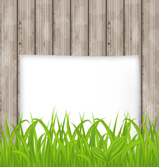 Green grass and paper sheet on wooden texture
