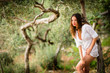 Attractive, young brunette on the beach, amid olive trees