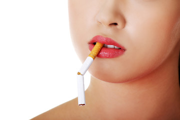 Young woman with broken cigarette in mouth