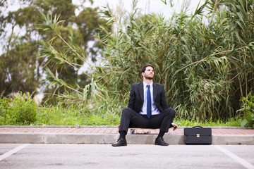 Businessman resting with his skateboard