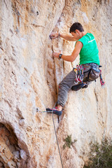 Young male rock climber on face of cliff