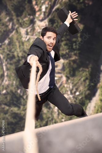 Leinwandbild Motiv Businessman holding a rope at the cliff