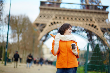 Young woman in Paris with coffee and croissant