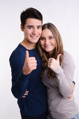 isolated studio portrait of young couple showing thumbs up