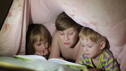 Boy reading a book to his brother and sister lying under a sheet