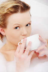 Woman relaxing in bath, drinking cup of coffee