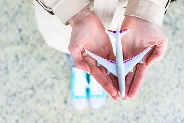 Closeup hand holding an airplane model at airport