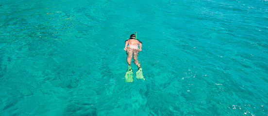 Beautiful girl snorkeling in clear tropical turquoise waters