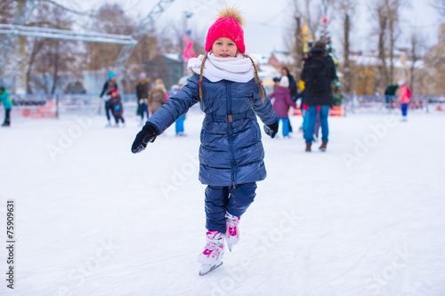Adorable little girl skating on the ice-rink - 75909631