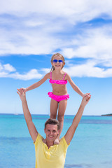 Young father and little daughter have fun during tropical beach