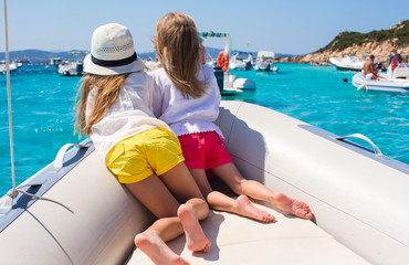 Little girls sailing on boat in clear open sea