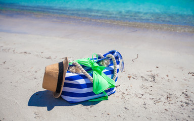 Stripe bag, straw hat, sunblock and towel on white tropical