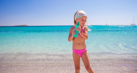 Little adorable girl in swimsuit with suntan lotion bottle