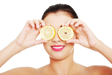 Portrait of nude woman with lemon on eyes