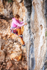 Young female rock climber on vertical cliff