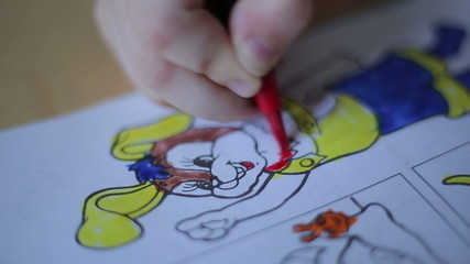 Little girl drawing with colored markers in the children's album