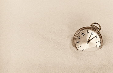 Antique timepiece in sand