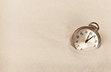 Antique timepiece in sand