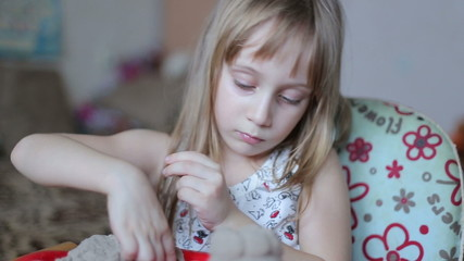 Little girl sculpts figures out of the kinetic sand, rolls palms
