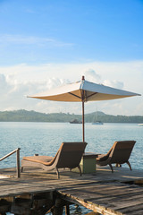 Two chairs and umbrella on wooden desk in resort ,Phuket